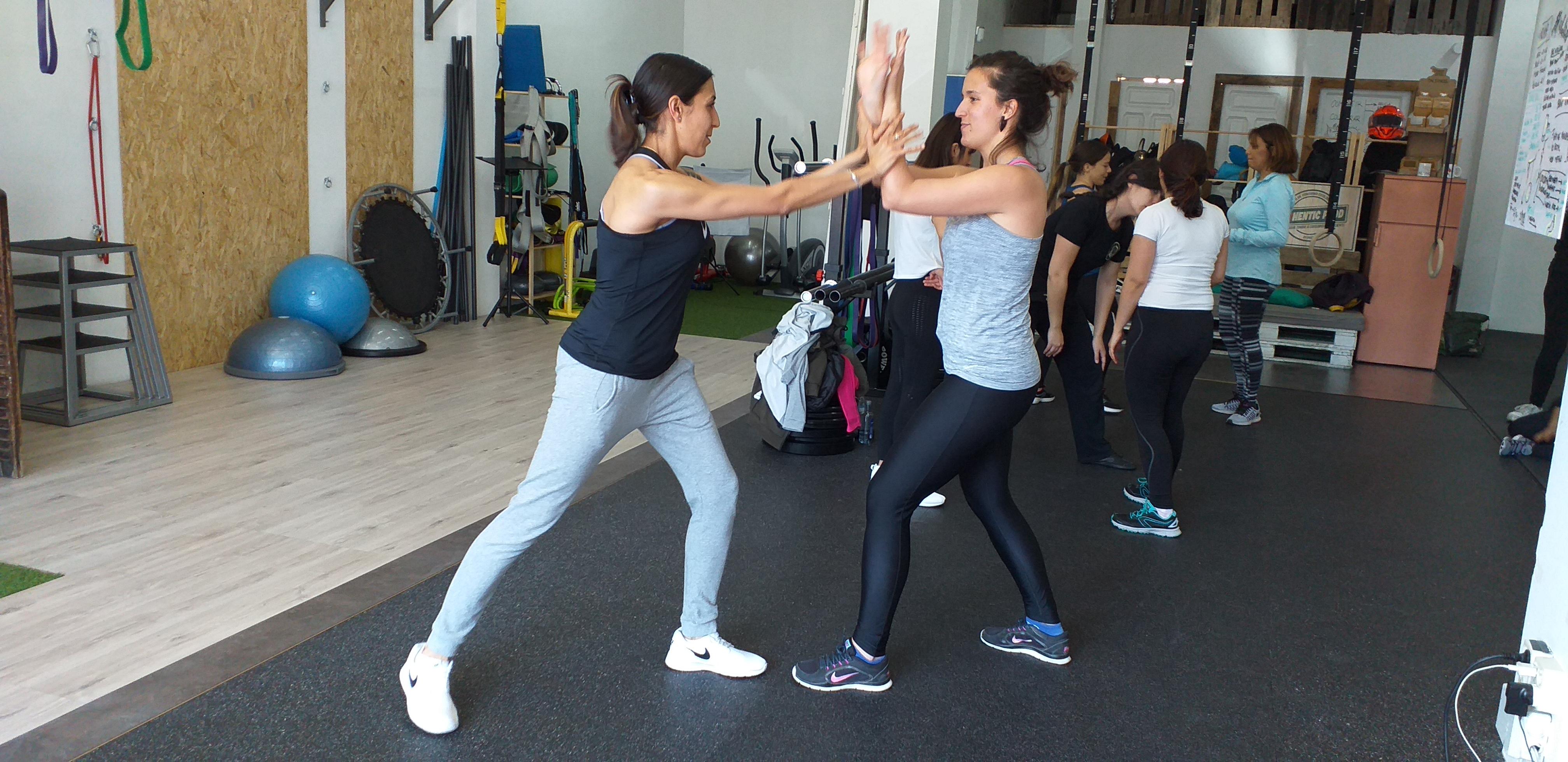 Dos mujeres practicando movimientos de defensa personal en un gimnasio.